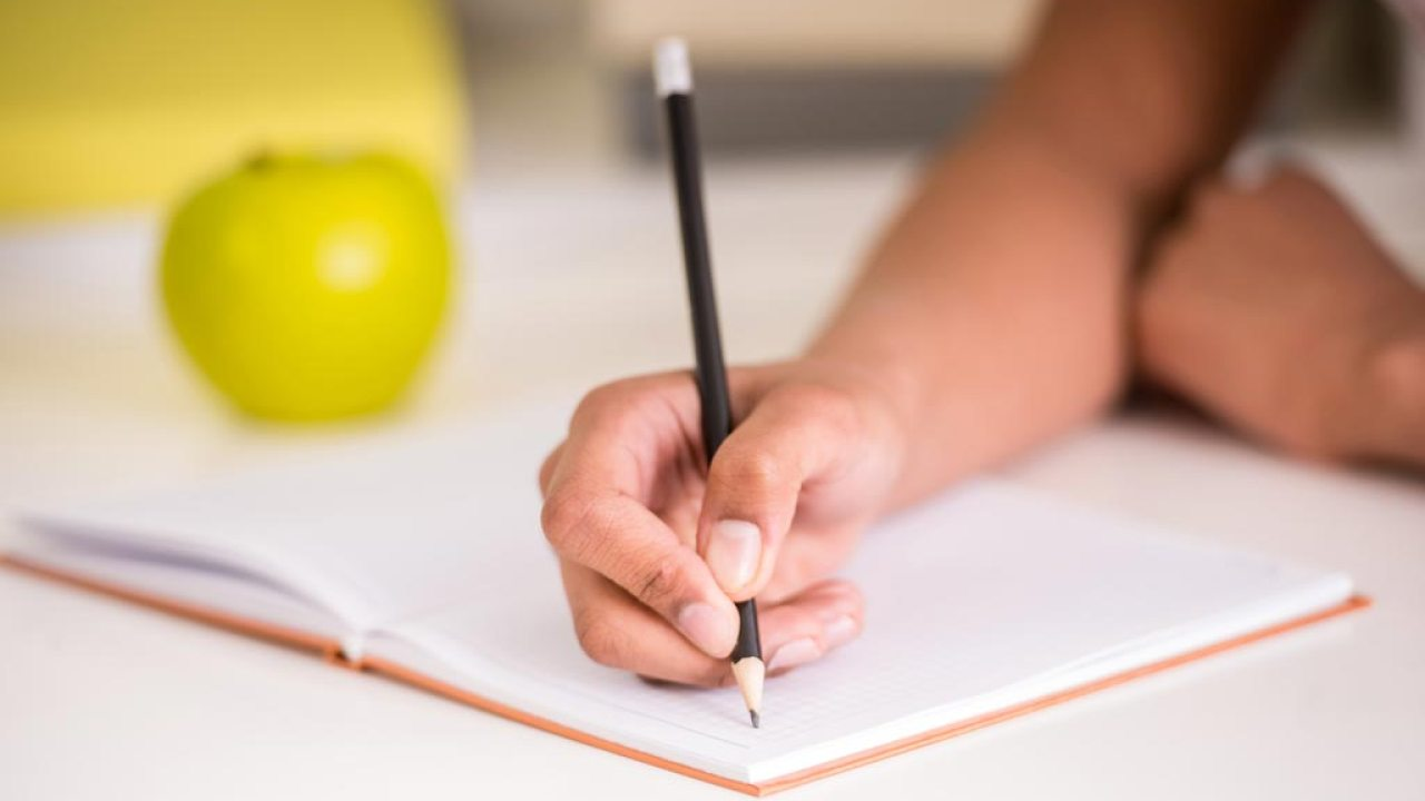 School.Homework.12_tricks_to_help_ADHD_kids_with_reading_writing_and_math.Article.5959C.girl_holding_pencil_writing.ts_474039096-1